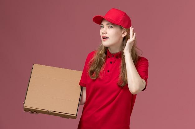 Courrier femelle en uniforme rouge essayant d'entendre la tenue de boîte de nourriture sur rose, travailleur de l'emploi de livraison de service uniforme