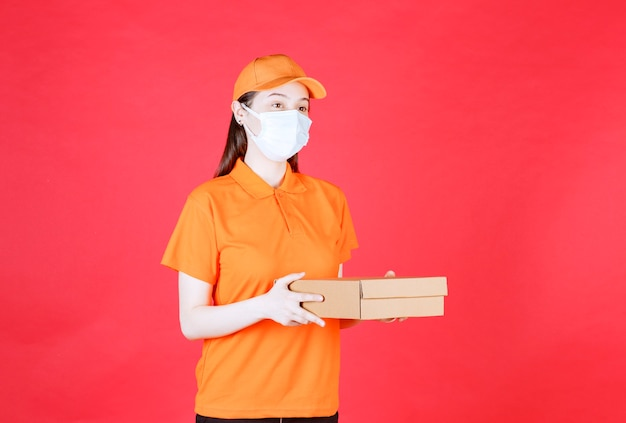 Courrier féminin en code vestimentaire de couleur orange et masque tenant une boîte en carton
