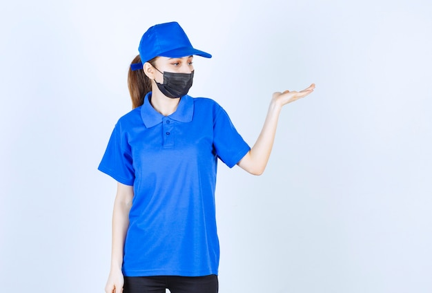 Courrier féminin en masque et uniforme bleu et montrant quelque chose sur le côté droit