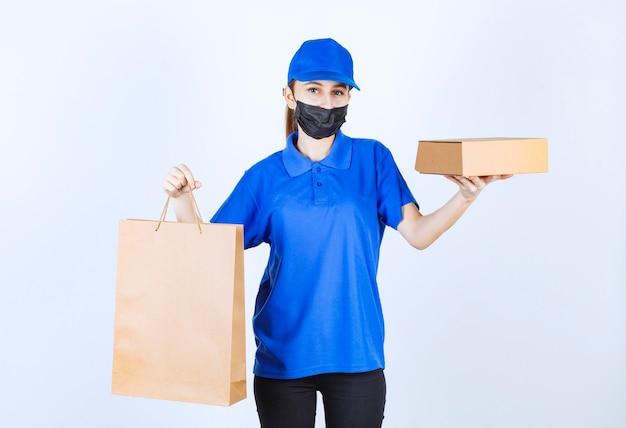 Courrier féminin en masque et uniforme bleu tenant un sac en carton et une boîte