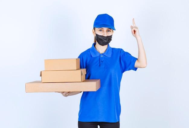Courrier féminin en masque et uniforme bleu tenant un stock de boîtes en carton et pointant quelque part