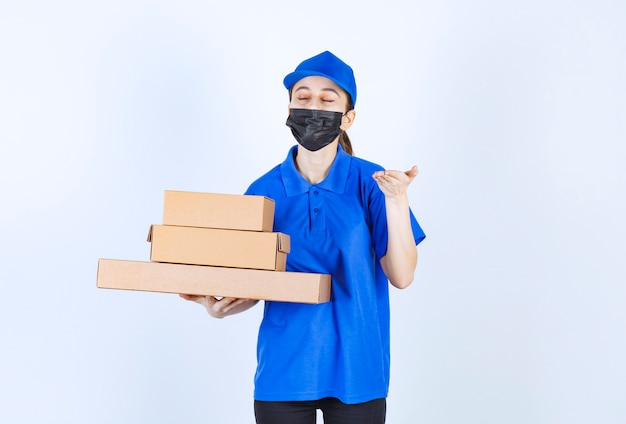 Courrier féminin en masque et uniforme bleu tenant un stock de boîtes en carton et sentant le produit.