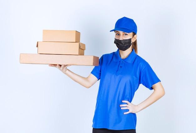 Courrier féminin en masque et uniforme bleu tenant un stock de boîtes en carton