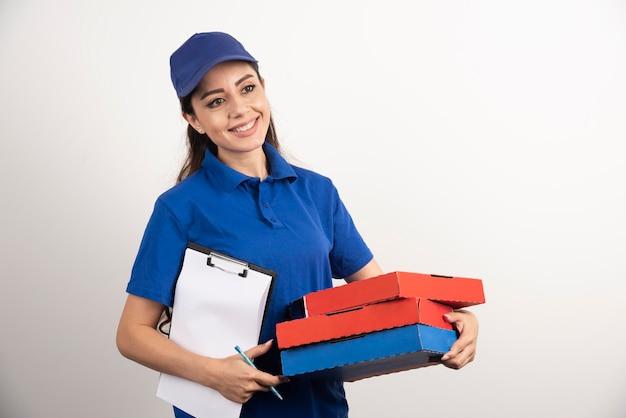 Courrier féminin positif avec carton de pizza et presse-papiers