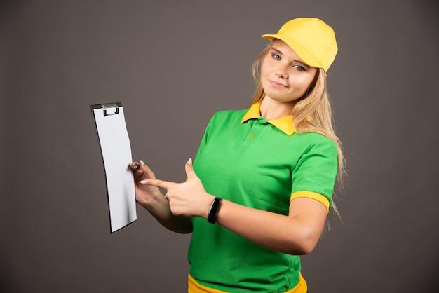 Courrier féminin souriant avec un crayon pointant sur le presse-papiers.
