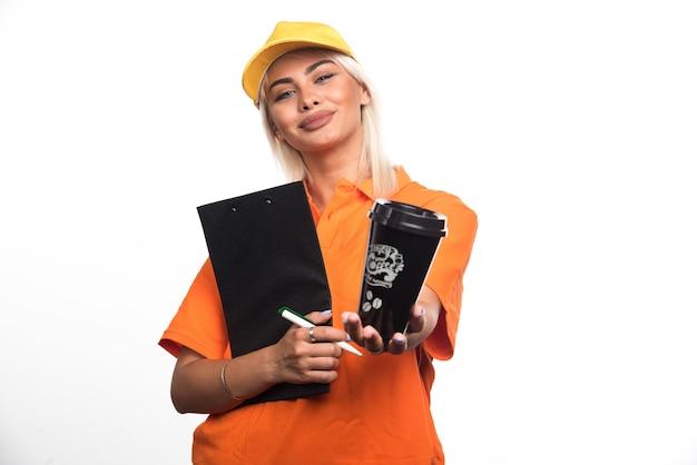 Courrier féminin tenant un cahier et donnant une tasse de café sur fond blanc. photo de haute qualité