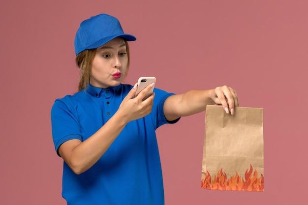 Courrier féminin en uniforme bleu à l'aide de son téléphone tenant un paquet de nourriture sur rose clair, travail de livraison uniforme de service