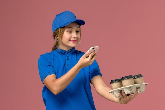 Courrier féminin en uniforme bleu en prenant une photo de tasses de café marron sur rose clair, la livraison d'uniforme de service de travail