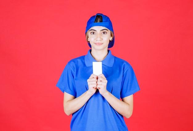 Courrier féminin en uniforme bleu présentant sa carte de visite.