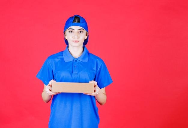 Courrier féminin en uniforme bleu tenant une boîte en carton.