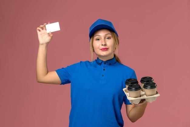 Courrier féminin en uniforme bleu tenant une carte blanche et brun tasses de livraison de café sur rose, livraison uniforme de travail de service