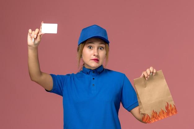 Courrier féminin en uniforme bleu tenant une carte blanche et un paquet de nourriture sur rose clair, livraison uniforme de travail de service