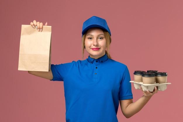 Courrier féminin en uniforme bleu tenant un paquet de nourriture et des tasses de livraison marron sur rose, livreur d'uniforme de service