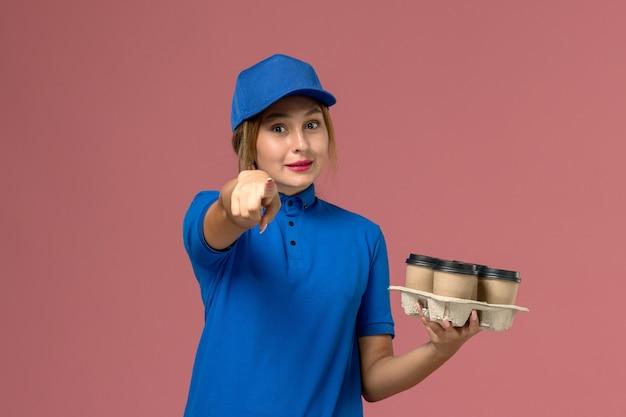 Courrier féminin en uniforme bleu tenant des tasses de café de livraison marron soulignant sur rose, travailleur de travail de livraison uniforme de service