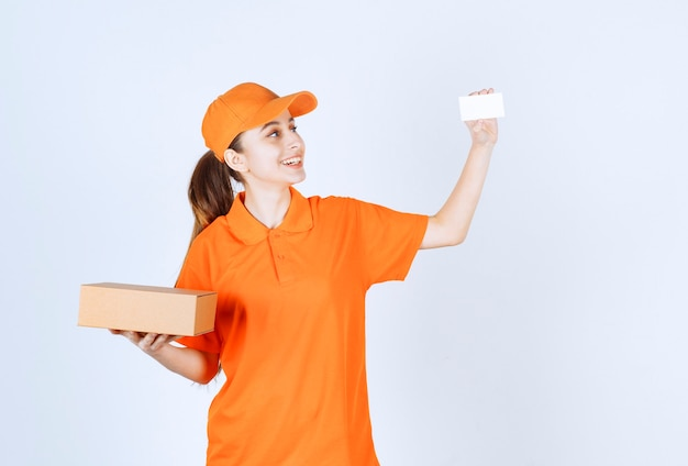 Courrier féminin en uniforme jaune livrant une boîte en carton et présentant sa carte de visite.