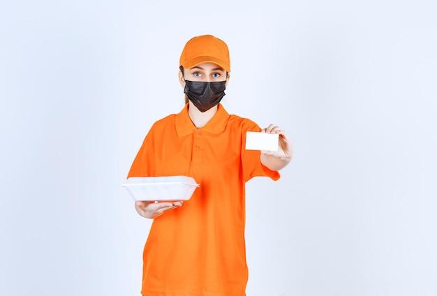 Courrier féminin en uniforme jaune et masque noir tenant une boîte de plats à emporter en plastique tout en présentant sa carte de visite.