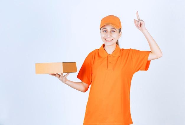 Courrier féminin en uniforme jaune tenant une boîte en carton et ayant une bonne idée.