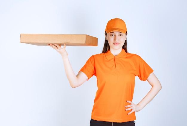 Courrier féminin en uniforme jaune tenant une boîte à emporter en carton.