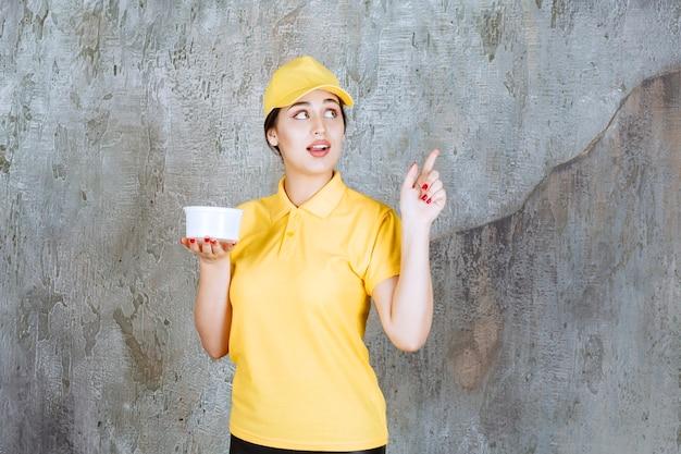 Courrier féminin en uniforme jaune tenant une tasse à emporter et pointant vers quelqu'un