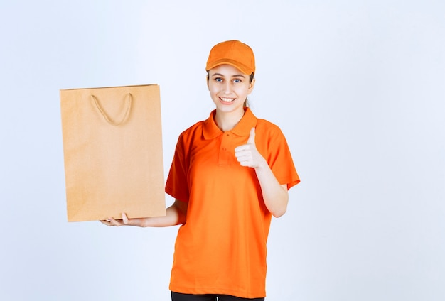 Courrier féminin en uniforme orange livrant un sac à provisions et montrant un signe positif de la main