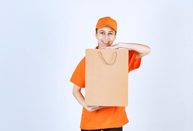 Courrier féminin en uniforme orange livrant un sac à provisions