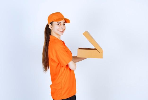 Courrier féminin en uniforme orange tenant une boîte en carton ouverte.