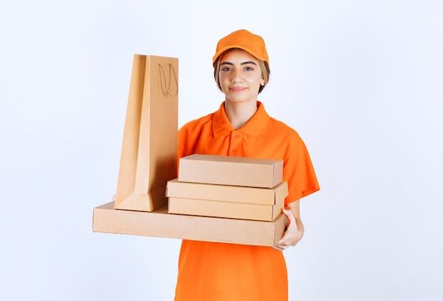 Courrier féminin en uniforme orange tenant un stock de colis en carton et de sacs à provisions