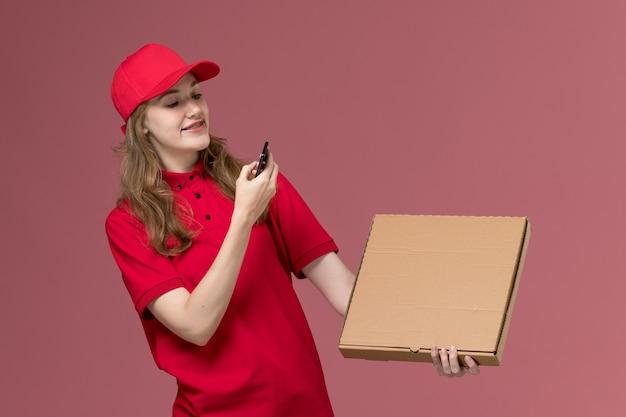 Courrier féminin en uniforme rouge en prenant une photo de la boîte de nourriture sur rose clair, la livraison des travailleurs de service uniforme de travail