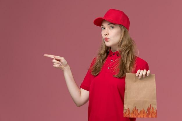 Courrier féminin en uniforme rouge tenant le paquet alimentaire sur rose, travailleur de l'emploi de livraison de service uniforme