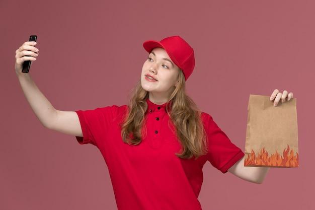 Courrier féminin en uniforme rouge tenant un paquet de nourriture et prenant selfie sur rose clair, prestation de travailleur de service uniforme de travail