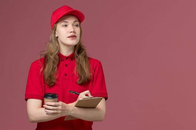 Courrier féminin en uniforme rouge tenant une tasse de café et un bloc-notes sur rose, travailleur de travail de livraison de service uniforme