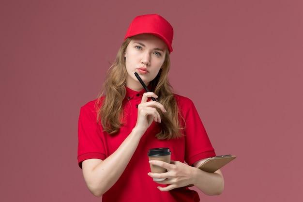 Courrier féminin en uniforme rouge tenant des tasses de café bloc-notes et stylo pensant sur rose, travailleur de travail de livraison de service uniforme