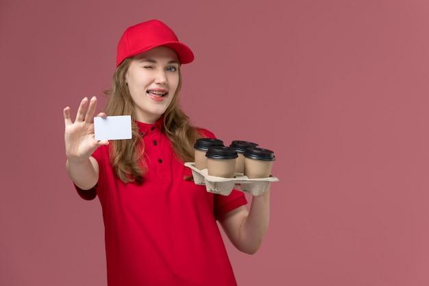 Courrier féminin en uniforme rouge tenant des tasses de café de livraison et carte en plastique blanc sur rose clair, fille de livraison de service d'emploi uniforme