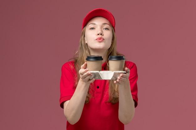 Courrier féminin en uniforme rouge tenant des tasses de café de livraison marron envoi de bisous sur l'air rose, travailleur de service d'emploi uniforme