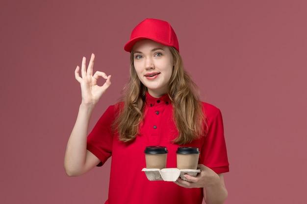 Courrier féminin en uniforme rouge tenant des tasses de café de livraison sur rose clair, uniforme travail service travailleur fille de livraison