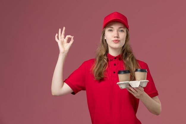 Courrier féminin en uniforme rouge tenant des tasses à café posant sur rose, travail de prestation de services uniforme