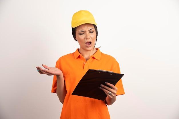 Courrier de femme choquée avec un crayon regardant sur le presse-papiers sur un mur blanc.