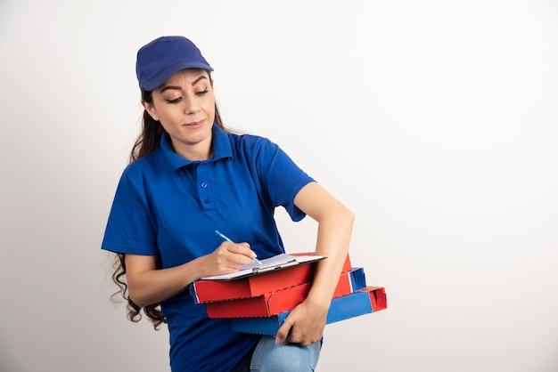 Courrier de femme écrivant dans le presse-papiers et tenant des cartons de pizza