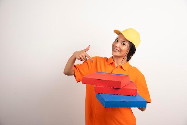 Courrier de femme pointant sur des pizzas sur un mur blanc.