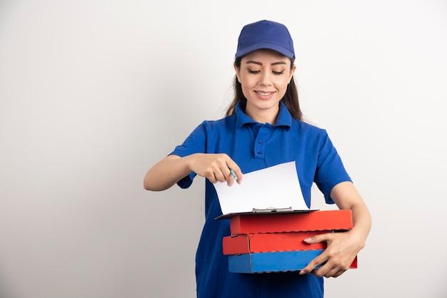 Courrier de femme regardant sur le carton de la pizza et du presse-papiers