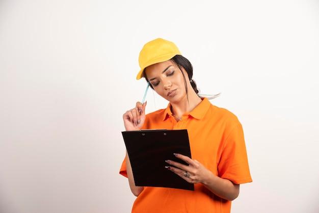 Courrier de femme sérieuse avec un crayon regardant le presse-papiers sur un mur blanc.