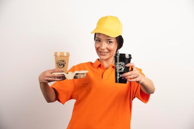 Courrier de femme souriante donnant deux tasses de café