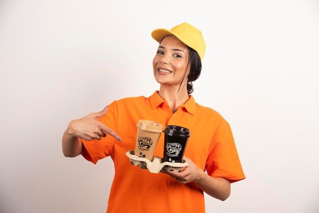 Courrier de femme souriante tenant deux tasses de café