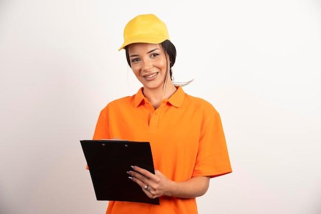 Courrier de femme souriante tenant le presse-papiers sur le mur blanc.