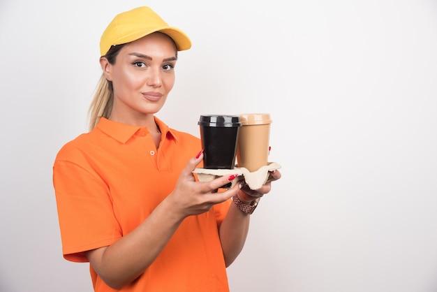 Courrier femme tenant deux tasses de cafés sur un mur blanc.