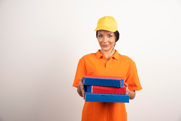 Courrier de femme en uniforme donnant des pizzas sur un mur blanc.