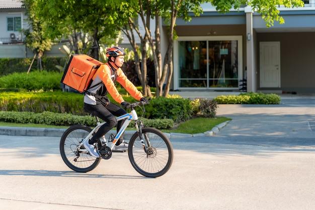Courrier homme asiatique à vélo livrer de la nourriture dans les rues de la ville avec une livraison de plats chauds à emporter et restaurants à la maison, livraison express de nourriture et shopping concept en ligne.