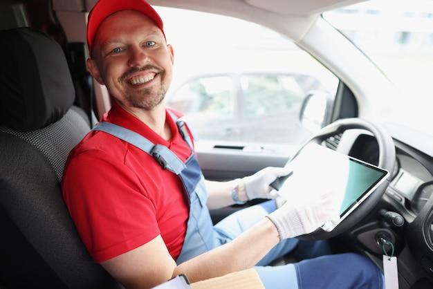 Courrier homme assis au volant de la voiture et tenant une tablette numérique dans ses mains
