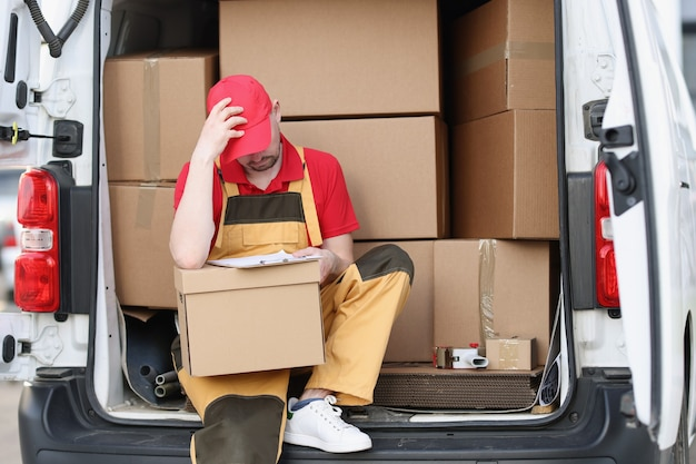 Courrier d'homme fatigué assis sur une voiture avec des boîtes en carton avec des documents dans les mains