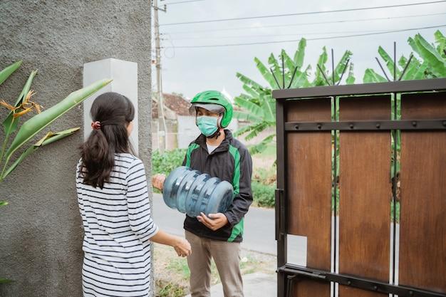 Courrier de l'homme offrant un gallon d'eau